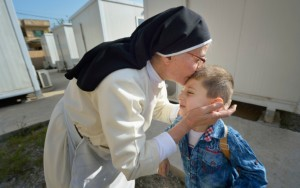 Dominican Sister Elene kisses 4-year old Luis Firas as he walks to a preschool in Ankawa, Iraq, April 7. The Dominican Sisters of St. Catherine of Siena were displaced by the Islamic State group in 2014 and have established schools and other ministries among the displaced. (CNS photo/Paul Jeffrey) See IRAQ-DOMINICAN-SISTERS-HOPE April 20, 2016.